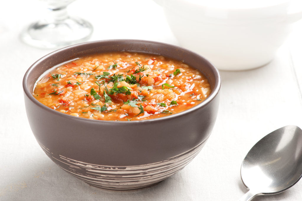 Weight Watchers Slow Cooker Stuffed Pepper Soups sits on top of a table in a gray bowl next to a spoon.